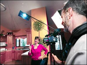 Zonya Foco tapes her show, Zonya's Health Bites, in her home kitchen. Her husband, Scott, is the cameraman.