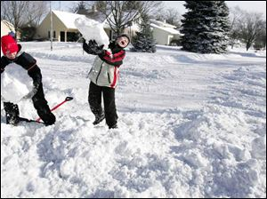 11-year-old Blake Rudolph, left, and Robert Herroon, 10, help clear snow from a neighbor s Whitechapel Street driveway.