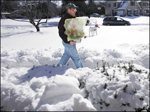 Bill Asendorf, of Joe Cooper Florist, carries an order of Valentine's Day flowers to a customer on Grand Valley Road in Maumee yesterday. Deliveries were stymied by the weather.