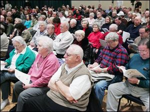 A large crowd hears about the potential financial impacts of a merger proposal for Sylvania and Sylvania Township.