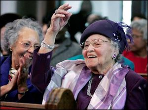 Dora Garner, left, applauds as her mom Lillian Russell-Jones is introduced at a special program at St. Paul Baptist Church.