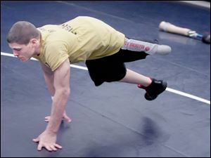 Napoleon s Brad Heinrichs does a bear crawl during wrestling practice after setting aside his prosthesis.