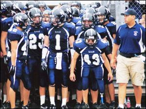 Brad Heinrichs (43) gets ready to lead Napoleon onto the football field. And coach John Snoad arranged a surprise finale.