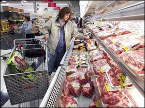 Tracey Doughten of Oregon shops in the meat department at Meijer in Oregon. Analysts say Meijer, Kroger, and other grocers are losing market share to Wal-Mart s grocery sales.
