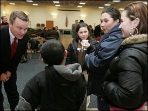 William Harner, the candidate who has been chosen to head the Toledo Public Schools system, introduces himself to Toledoans Jesus Avila, 8, Jessa Avila, 10, their mom, Tammy Avila, and Sierra Avila, 15, at a recent reception at Waite Brand mAuditorium.