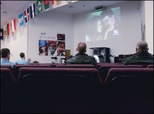 Firefighters and police offi cers watch the funeral on a church TV screen. Toledo s four television