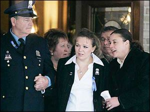 Danielle Dressel, widow of Detective Keith Dressel is escorted from the funeral home.