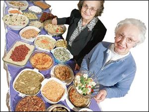 Mary Markham and Ann Mulopulos with some of their potluck dishes.