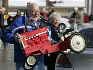 Fritz Vogel of St. Marys, Ohio, carries a pedal tractor purchased by Lucy Gray to her car. Ms. Gray is one of about 3,000 people expected for the Toy and Doll Show, which ends today at 3 p.m.