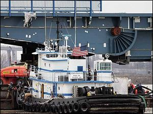 Workers unhook the tug John Francis as it turns a drawbridge section before pushing it into position on the Martin Luther King, Jr., Bridge today.