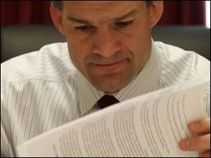 U.S. Rep. Jim Jordan examines documents during a break in meetings on Capitol Hill in Washington.