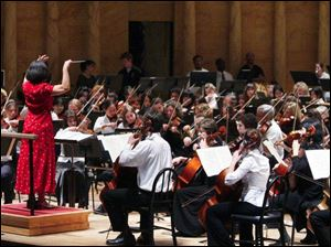 Elizabeth Hamaker conducts during rehearsal of the combined Toledo Symphony and Toledo Youth Orchestra.