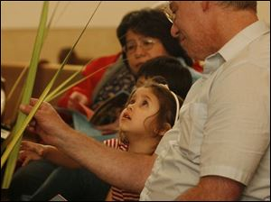 Slug: CTY Palms31p  Date:  03/31/2007   Location:  Toledo, OH  Caption: THE BLADE/ERIC SUMBERG  Destiny Ball, 3, looks at her palm with her grandfather Brad Ball at the Palm Sunday service at St. Lucas Evangelical Lutheran Church in America on Saturday.   Sunday is Palm Sunday, the start of the Holy Week that leads into Easter Sunday, a day in which Christians remember Jesus' triumphant entry into Jerusalem with the people waving palms.         Summary:  Palm Sunday service at St. Lucas Evangelical Lutheran Church in America led by Pastor Martin E. Billmeier.