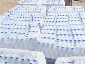 Bottles of water arrive in huge, blue cubes bundled into thousand-bottle units by a 5-foot roll of industrial cling wrap. This water is processed in a plant on the edge of base, and it is distributed by racing forklifts.