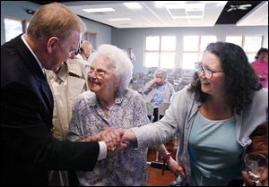 Gov. Ted Strickland greets Elizabeth Smith and her daughter-in-law, Toni Smith, at the Mayores Senior Center, where he talked about his proposed tax cut for seniors yesterday.