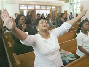 Carolyn Hobbs raises her hands in prayer at a recent Wednesday evening service at Upton United Methodist Church.