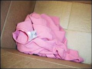 This pink sweater also was found in the cardboard box with the baby boy.