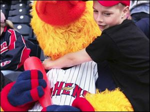 Nick Gibb, 11, gives Muddy a hug in the stands of Fifth Third Field as the Toledo Mud Hens host the Louisville Bats. Nick and some of his classmates from St. Joan of Arc School attended yesterday s game, which the Bats won 5-4.