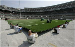 FieldTurf specialists install the new synthetic surface for Ohio Stadium, which has used natural grass since 1990.