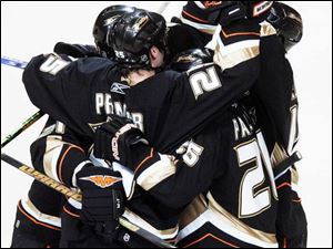 Ducks center Rob Niedermayer, back right, is mobbed by teammates after scoring a goal in the first period last night as Anaheim beat Detroit to advance to the Stanley Cup finals.
