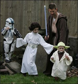 Reese, 4, Reagan, 8, Corinne, 2, and their dad Mike Shull, in their Star Wars costumes in his Scottwood home backyard.