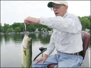 Marion Garber, a veteran bass fisherman from Temperance, Mich., hefts a largemouth bass hooked on Evans Lake in the Irish Hills, using a treble-hook-filled crankbait. A Rattlin' Rogue is a popular and successful bass crankbait.