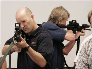 Matthew Haschak, left, and other FBI Citizens  Academy members learn how to handle weapons