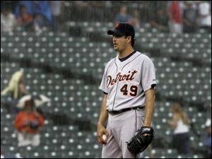 Detroit s Jason Grilli seems to be a little frustrated as the umpires call for the tarp with two outs