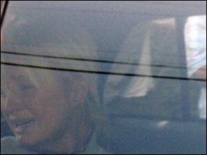 Paris Hilton weeps in a police car as she is taken from her Hollywood Hills home to Los Angeles County Superior Court.