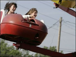 Lauren Altenburger, 12, left, and Rachel Langenderfer, 12, both of Maumee, take a ride at the Whitehouse Cherry Festival.