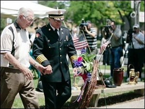 John Timmers, 91, whose firefighter father was killed while on a run in 1916, is escorted to the wreath -placing ceremony by Acting Chief Michael Wolever during the memorial service at Chub DeWolfe Park.