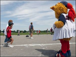 Schyler Young gets some encouragement from Muddonna, one of the Toledo Mud Hen baseball team's mascots who came out for the Miracle League of Northwest Ohio's finals. Schyler is accompanied by volunteer Patricia Pokrzywa on the trip around the bases.