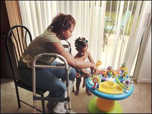 Vena Lampkin, permanently disabled in an accident in Toledo last year, plays with her young daughter Rashyra.