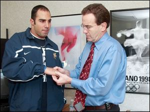 Dr. Roger Kruse, right, examines the throwing hand of former