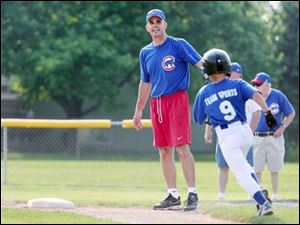 L.J. Archambeau tells his son, Tyler, to round first and head for second during a Little League game at Fairfield Elementary School. Coaching the team gives him time with his son and a chance to help others, too.