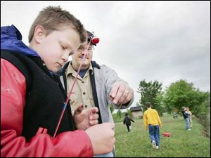 Cubmaster Mike Kleman helps Michael Calcamuggio, 10, during a Boy Scouts fishing outing at a pond in Bowling Green.