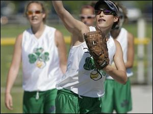 Olivia O Reilly throws a softball while warming up with her