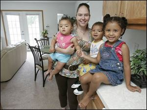 Aimee Przybysz and children Jayla Shuman, 1, left, Jamall Shuman, 2, and Jazmine Shuman, 4, in a new four-bedroom home.