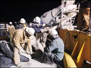 A group of workers seals the final segments of the bridge together in December, 2006. Linda Bowyer, an associate professor of finance at the University of Toledo, says the nearly $98 million in wages and benefits paid on the project produced benefits in Toledo and surrounding counties in the form of a spending spree.