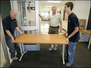 Principal Gary Devol, center, assists Vince Whitacre, left, and Todd Polker inside the new Keyser Elementary School.