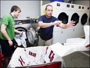Jake Garber, and Mud Hens clubhouse manager Joe Sarkisian wash the players uniforms after the game.