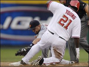 Former Tiger Dmitri Young beats the tag of Placido Polanco for a double in the second inning last night at RFK Stadium.