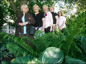 Maumee Garden Club members, from left, Darlene Carpenter, Connie Barron-Smith - whose garden is pictured - Marcia McCready, Susan Utterback, and Sara Becker celebrate the group's 75th anniversary.