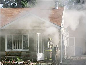 A Toledo firefighter enters the burning Katafiasz home this morning.