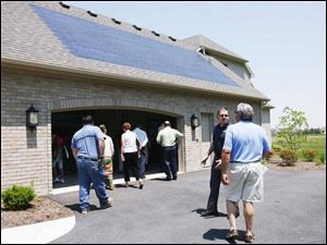 Frank Kozak and Keith Haddad, foreground from left, discuss the solar shingles on the home as others enter it.