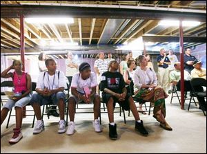 Steffanye Hicks, Shaquille Clemons, Antonia Draper, Jordan Walker, and Lori Shaw, from left above, of Englewood Peace Robotics Engineering Team, listen during a presentation in the basement of an energy-efficient house.