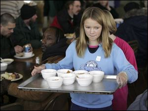 A young volunteer serves a dessert during Thanksgiving 2006 at the Cherry Street Mission Community and Food Services Building. Volunteers, like this girl, have been helping the center meet its mission since 1947. Sixty years later, the need for its ministries is larger than ever.