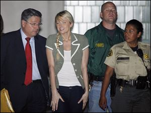 Escorted by lawyer Richard Hutton, left, and two sheriff s