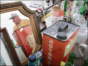 That's Tom Huff of Berkey, Ohio, shown in the mirror, among his offerings in the Historical Old Territorial Road garage sale.