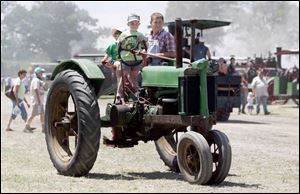 Ben Harbauer, 6, steers one of the family tractors as sister Anna, 3, and dad Jim ride along.